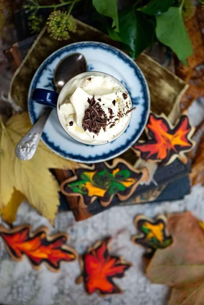En kop varm chokolade omgivet af småkageblade og efterårsblade