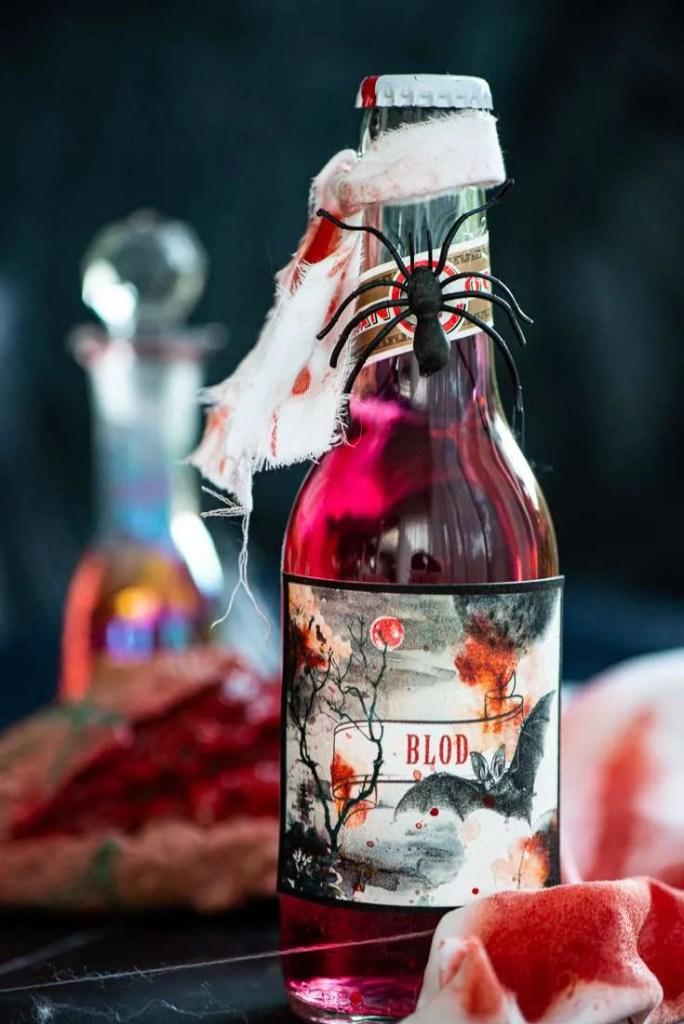 Flasken med blodrød sodavand er pyntet med en stump hvidt stof med blodstænk