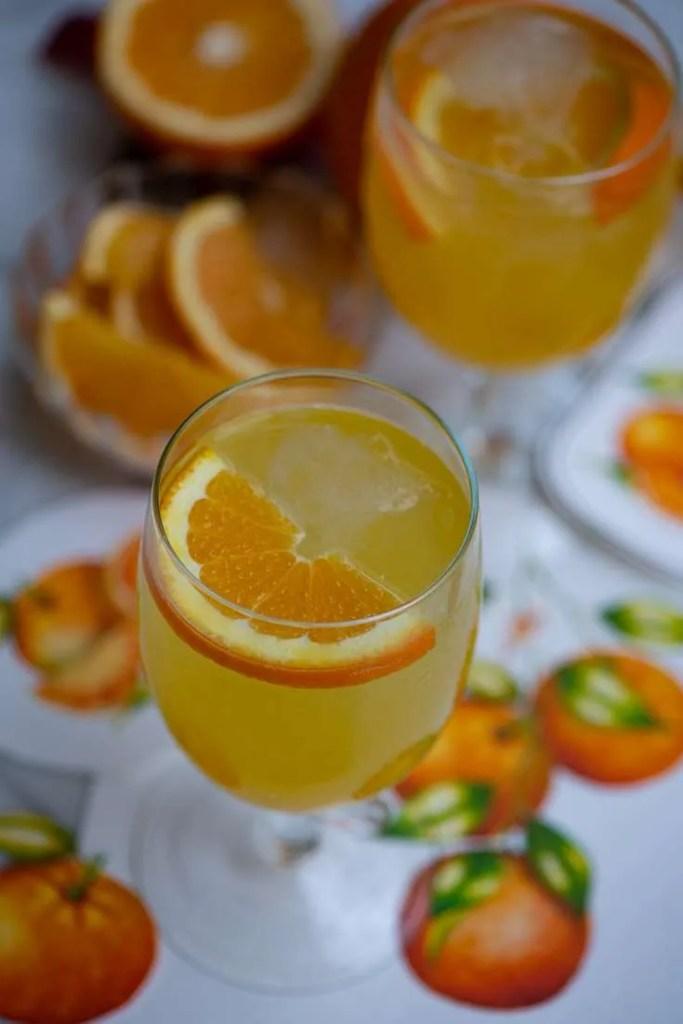 Opskrift på hjemmelavet orangeade. På billedet er der to glas med frisklavet orangeade omgivet af friske appelsiner