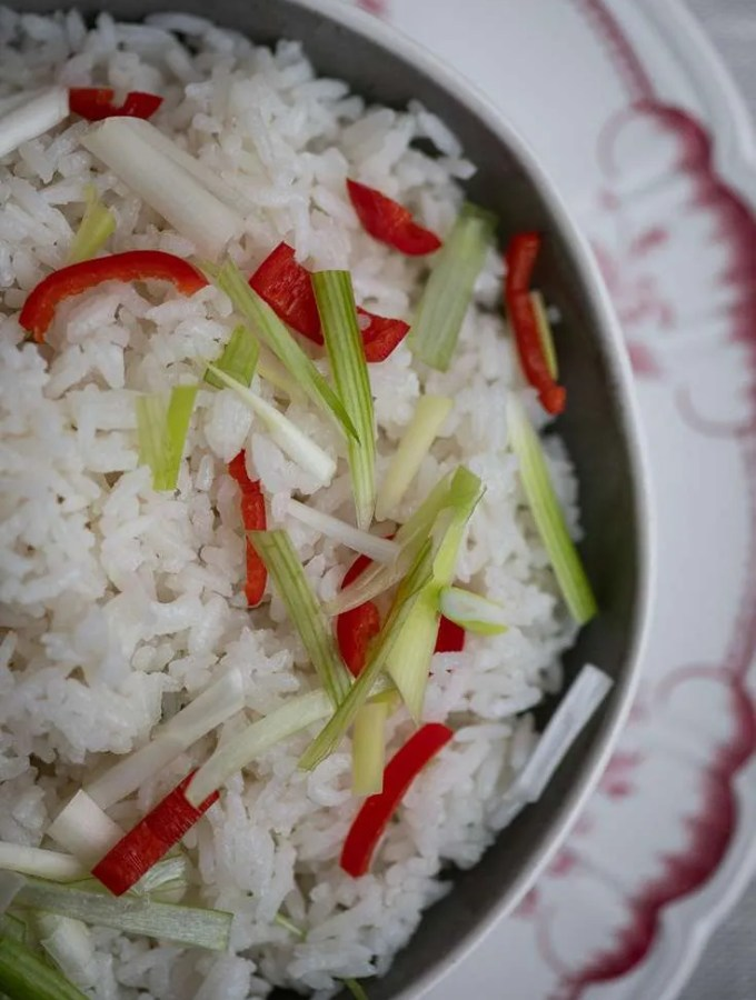 En skål lækre kokosris drysset med lidt urter på toppen