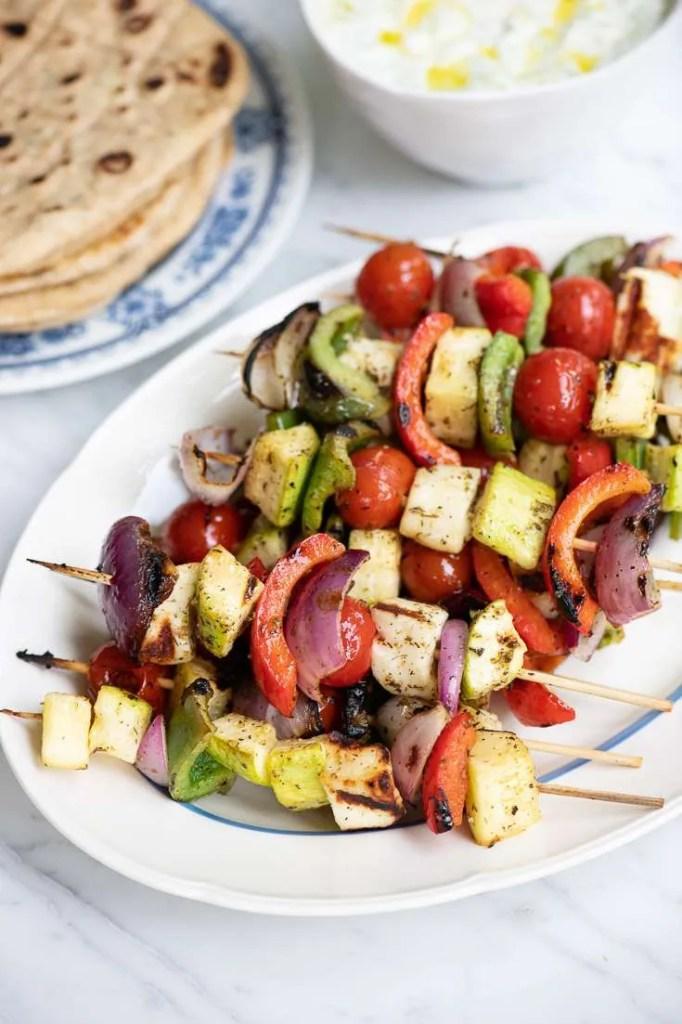 De græske grøntsagsspyd med græske pitabrød og tzatziki i baggrunden