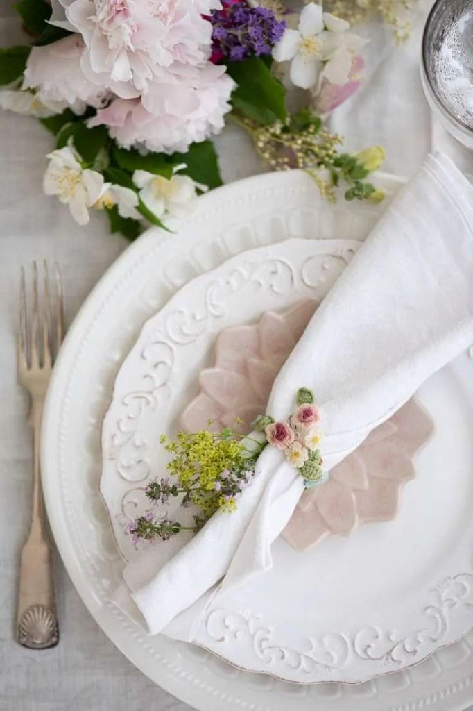 Bordet er dækket til en hyggelig middag i juli med pæoner og lyserøde tallerkner
