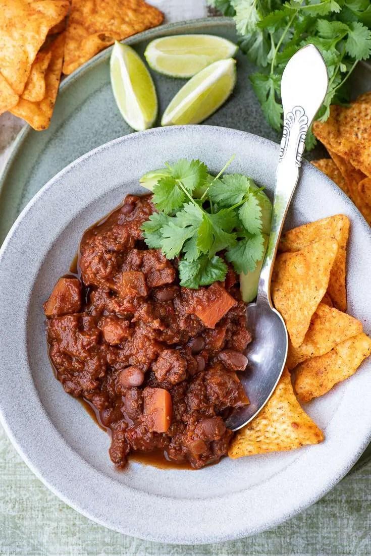 Opskrift på chili sin carne. Her serveret i en skål omgivet af tilbehør