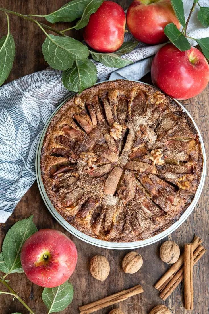 Den lækre æblekage omgivet af æbler, valnødder og kanel