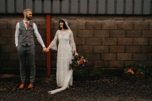 Bride and groom standing holding hands