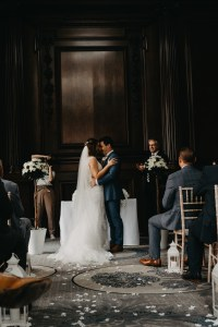 a bride and groom standing at the top of the aisle with their heads together