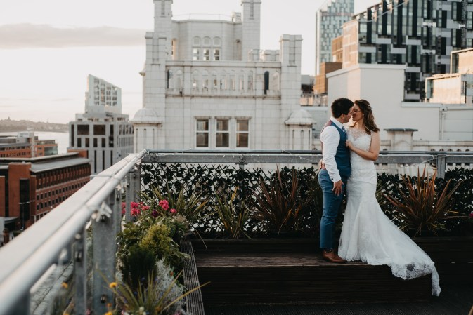 A bride and groom kiss on a rooftop