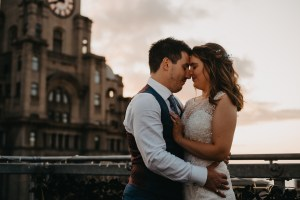 A bride and groom presses their heads together on a rooftop in Liverpool City Center