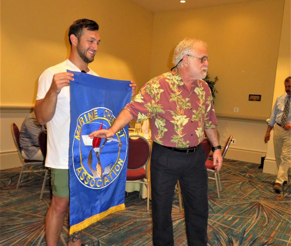 Les Blaize Explaining the Meaning of the MCA Logo. Trainee Nick Hernandez, holds the Banner