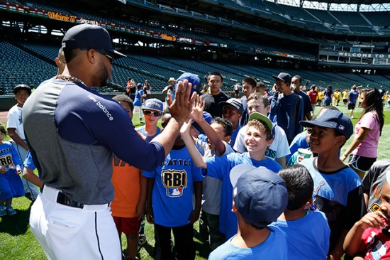 Kids from the Seattle RBI program get high fives from Robinson Cano during the PLAY event at Safeco Field.