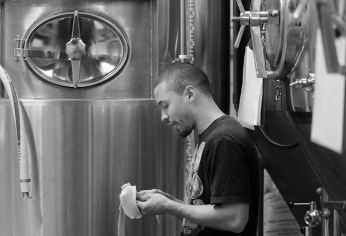 Brew day is a frenetic dance of multitasking as beer is brewed, empty tanks are cleaned and kegs are filled for shipment. Wong refuels with a banana.