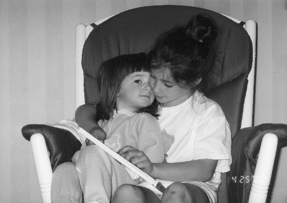 sisters reading on rocking chair together