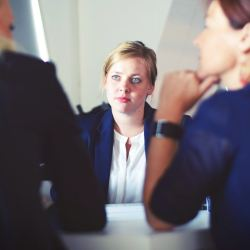 Three businesswomen talking at a white table