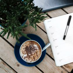 writing in free time with notebook and coffee on desk