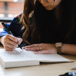 resources for serious freelance writer, girl writing on at desk
