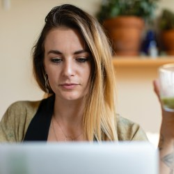 woman on computer with drink, badass career