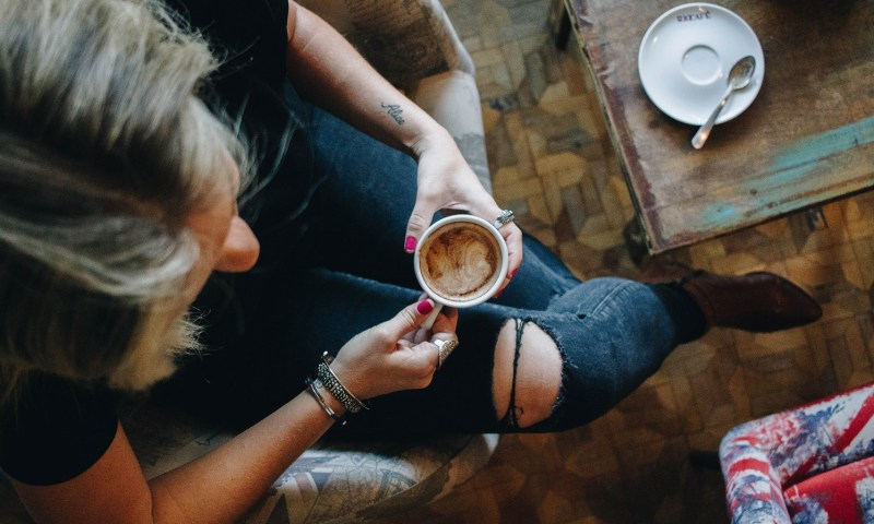 woman holding coffee over table
