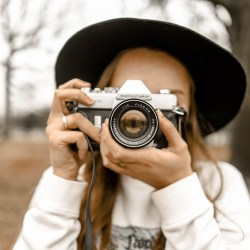 woman holding camera in front of face, how to get out of a creative rut