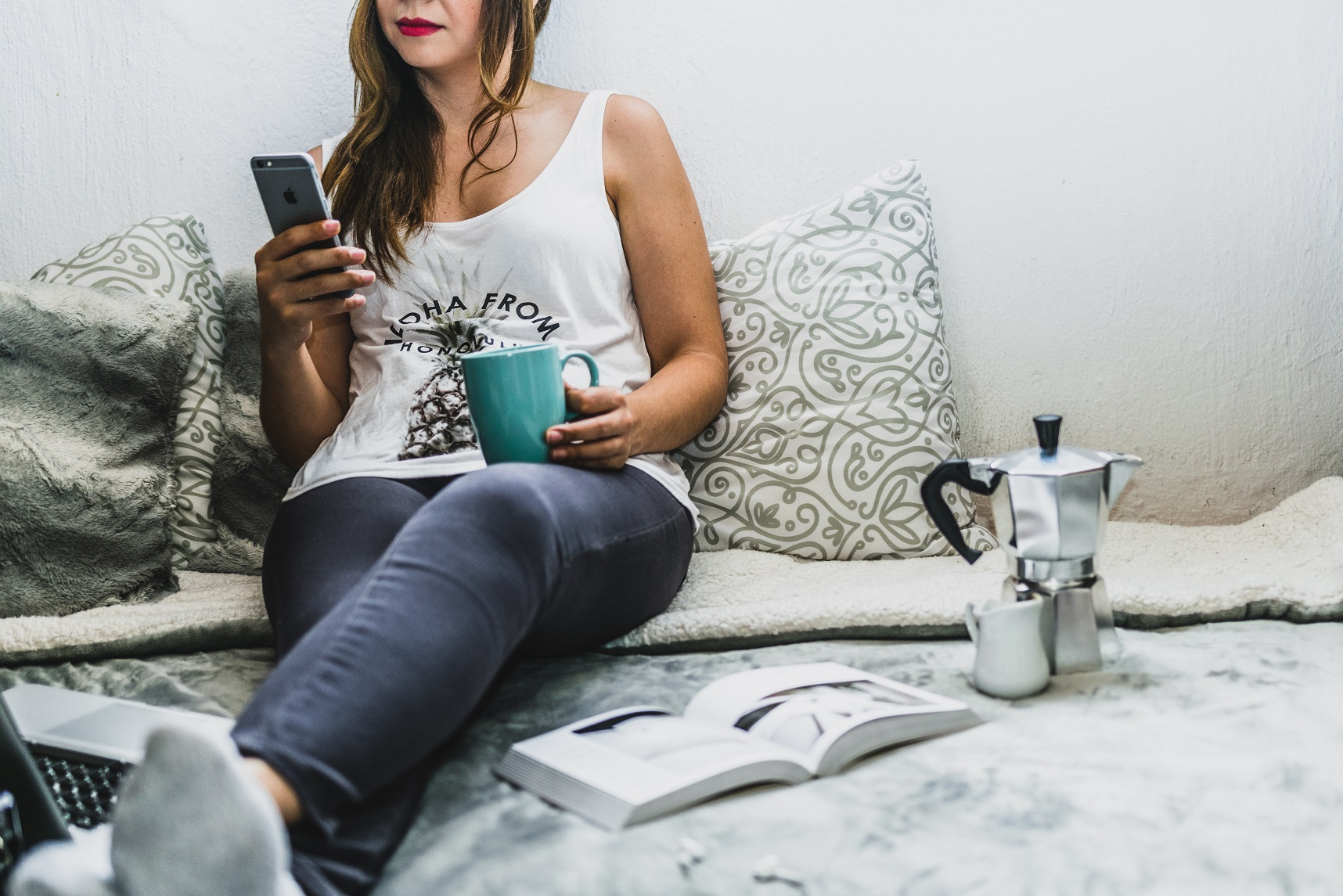 woman sitting on bed with phone writing shareable blog content