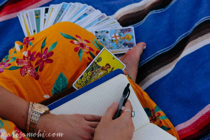 A woman's lap holding a notebook with tarot cards spread out beneath her knee.