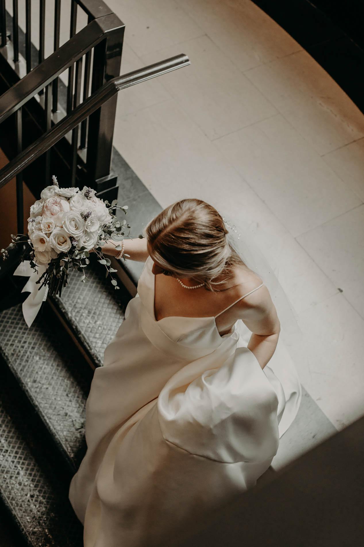 bride walking down black marble stairs