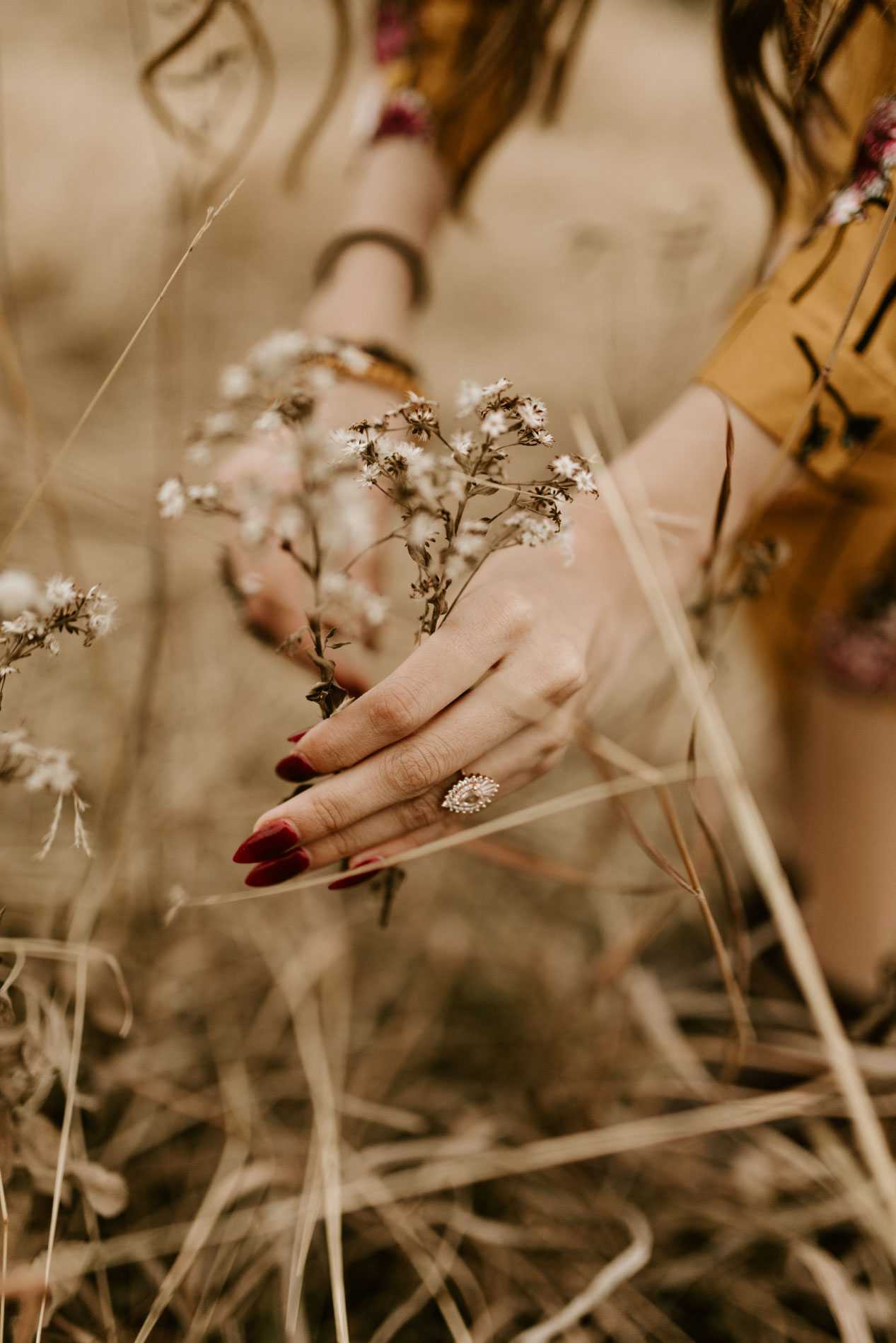 girl picking flowers wearing an engagement ring