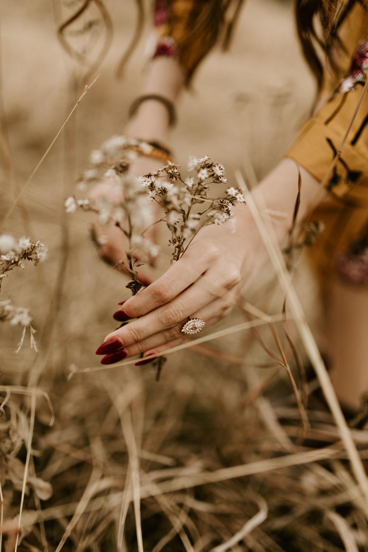 girl picking flowers wearing an engagement ring