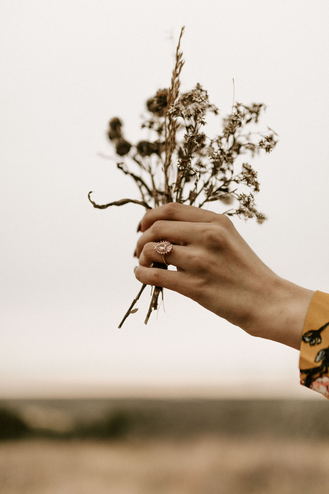 girl holding flowers with heidi Gibson engagement ring