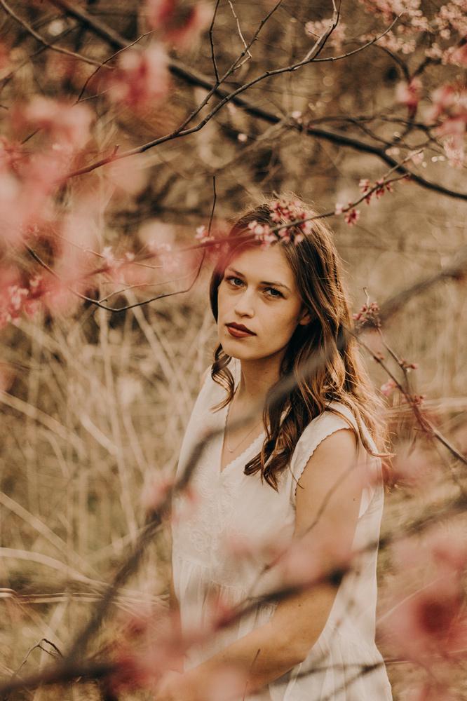 photo of girl through cherry blossom