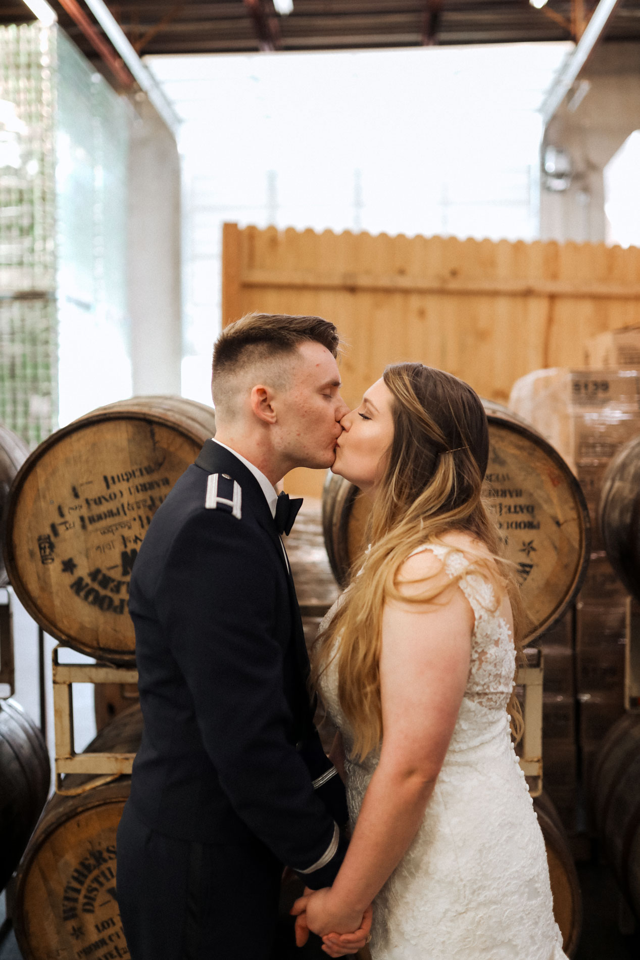 bride and groom kissing inside brewery