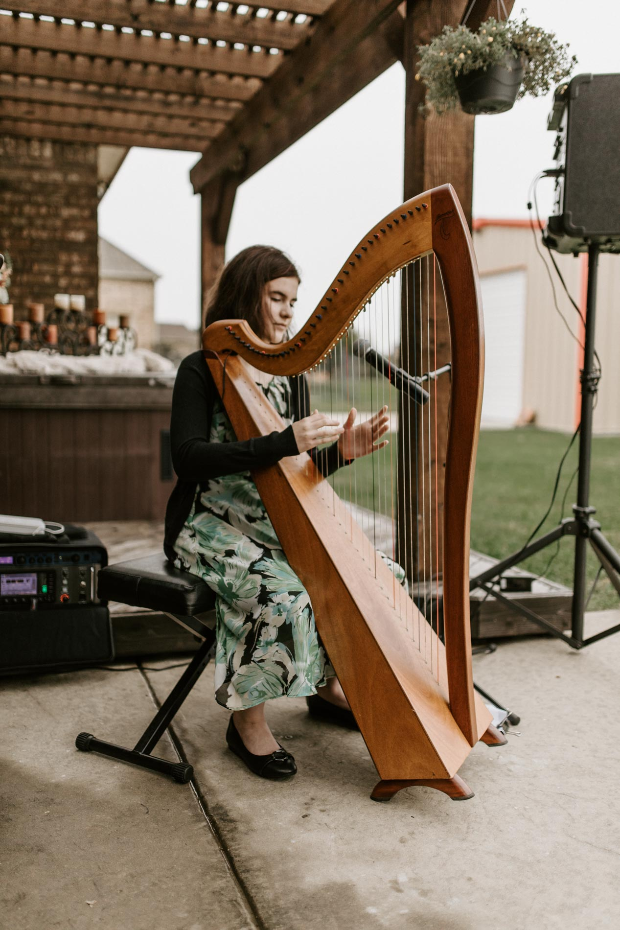 Beautiful harpist at backyard outdoor wedding