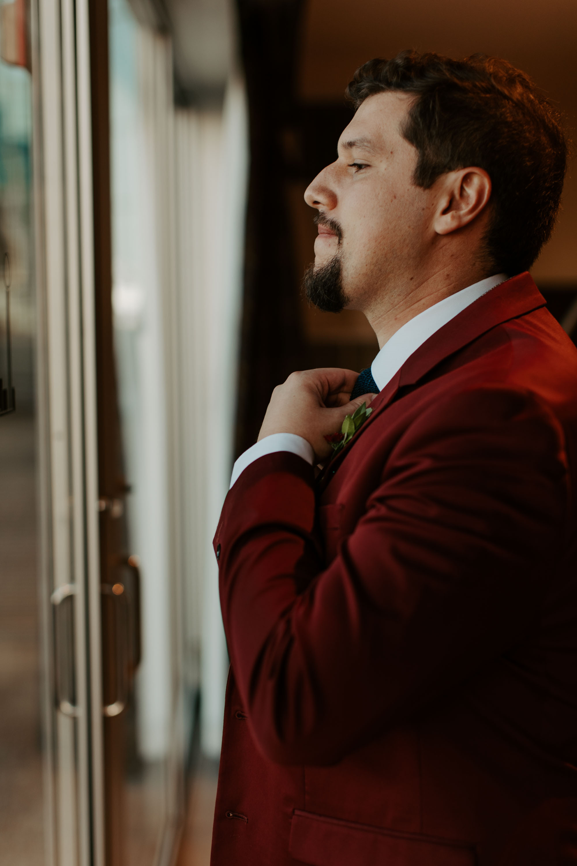 Groom putting on suit and tie before wedding day