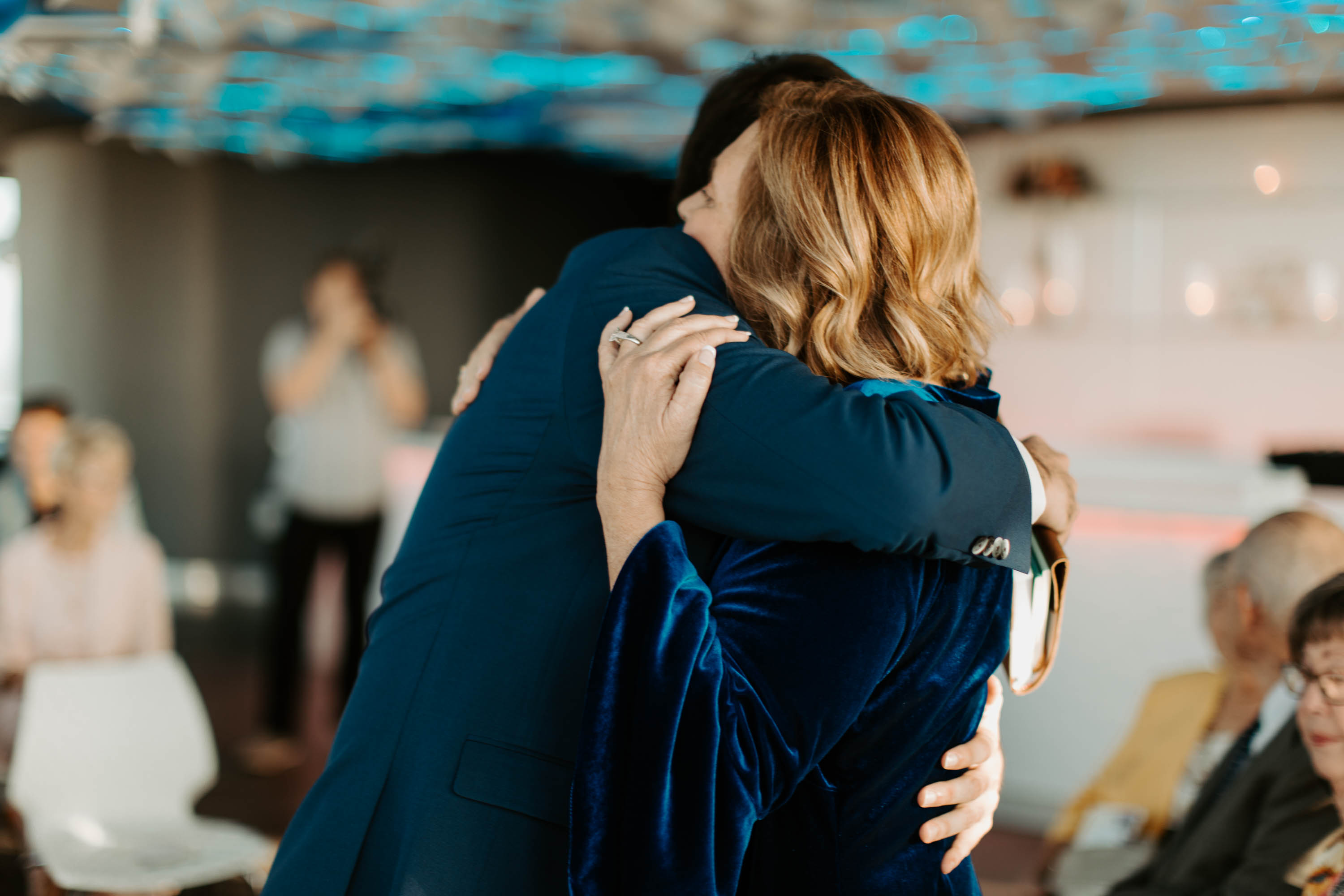 Mother hugging son after he walks her down the aisle at reunion tower