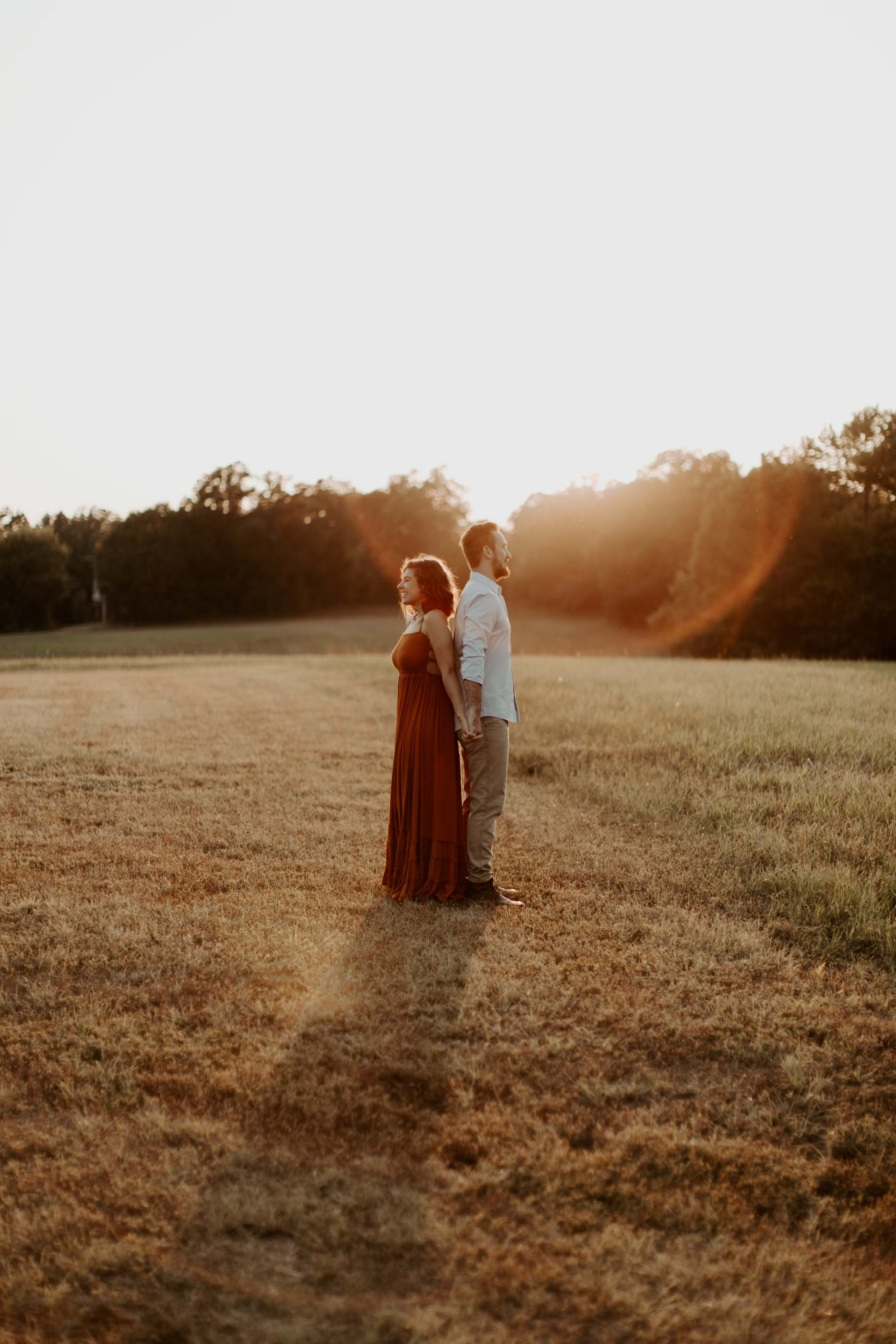 couple standing back to back at golden hour for artistic photo