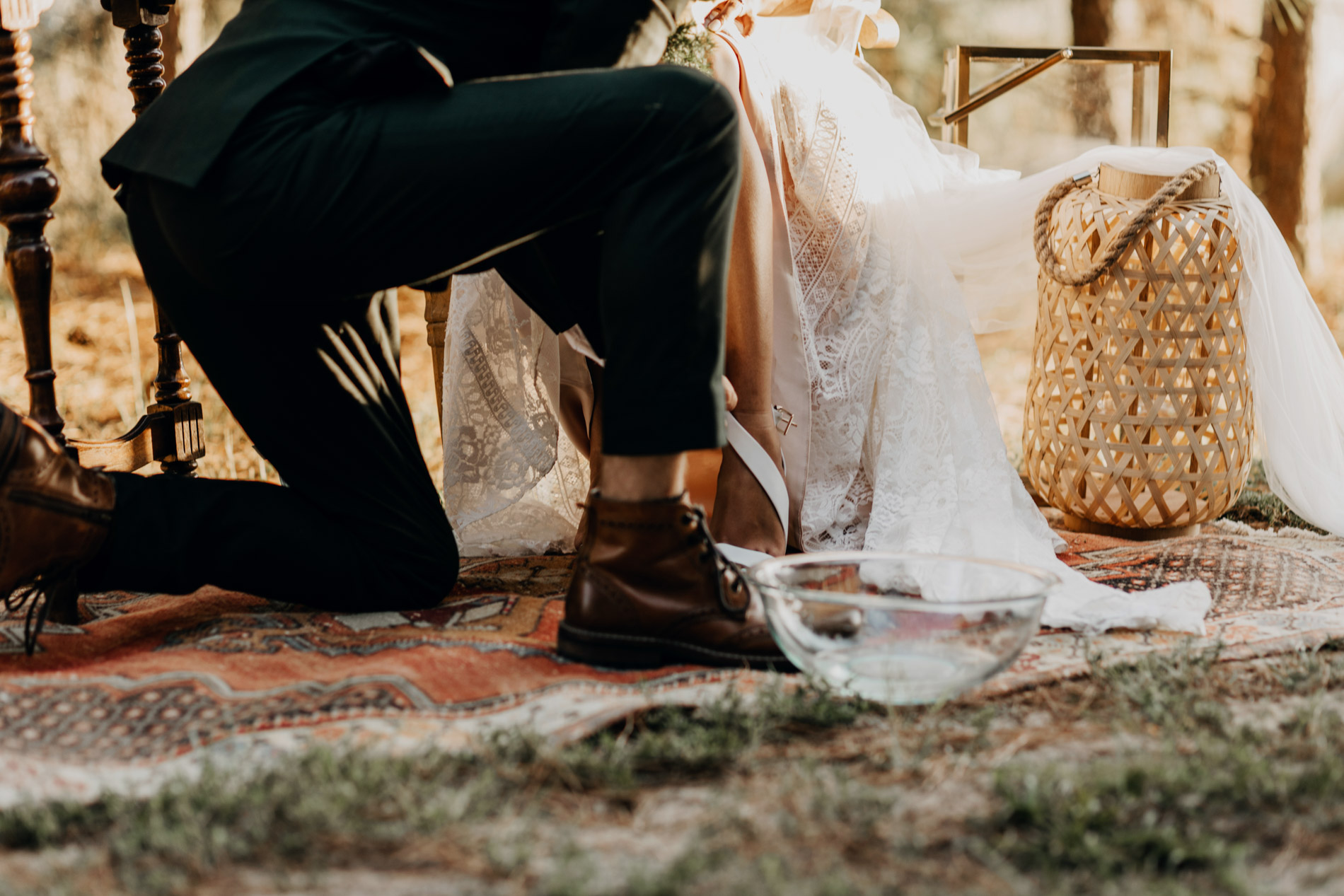 Groom washing brides feet during wedding ceremony