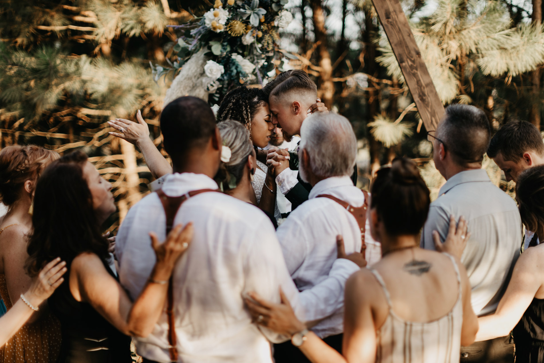 Bride and grooms family praying around them on wedding day