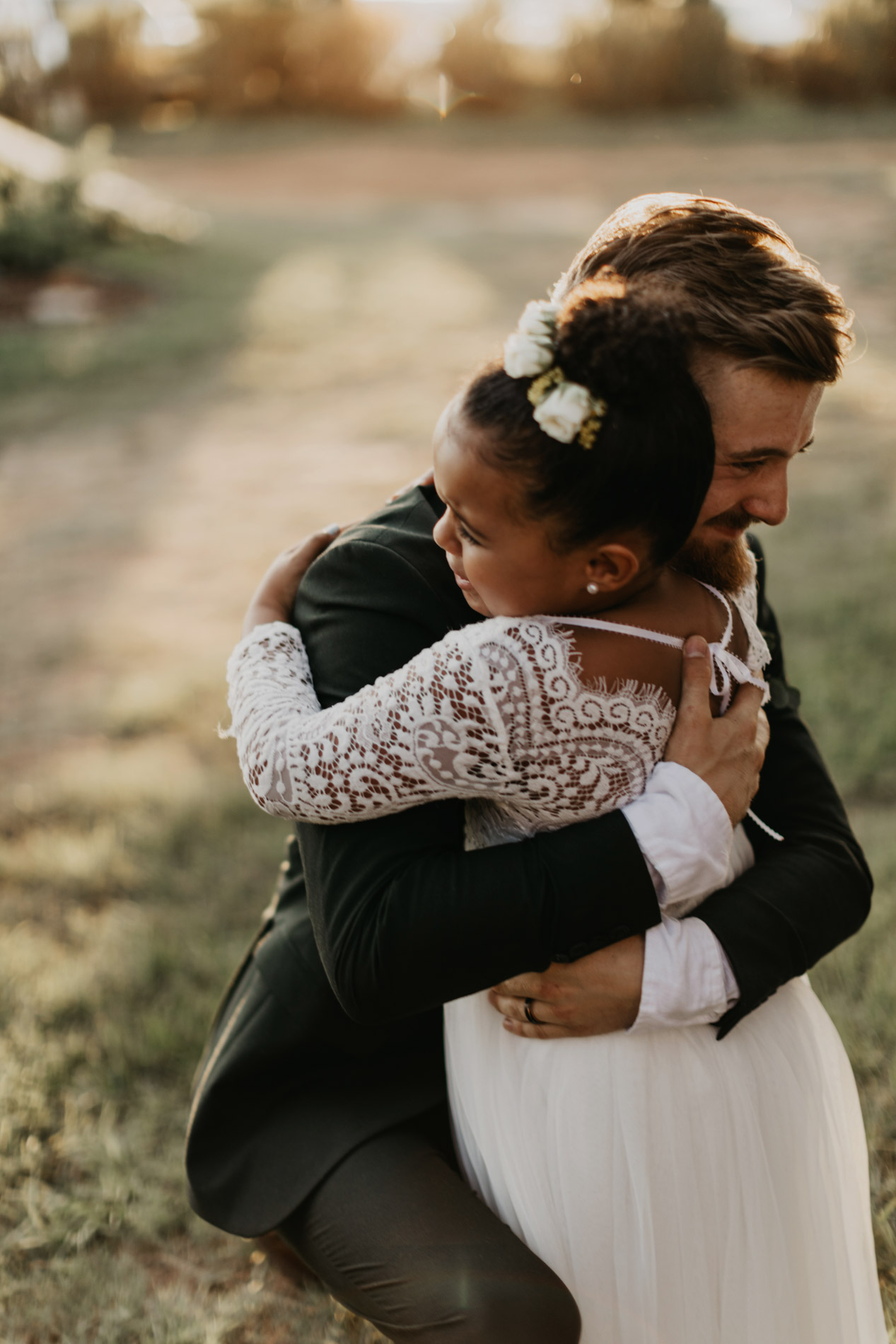 Groom hugging brides little sister after wedding ceremony