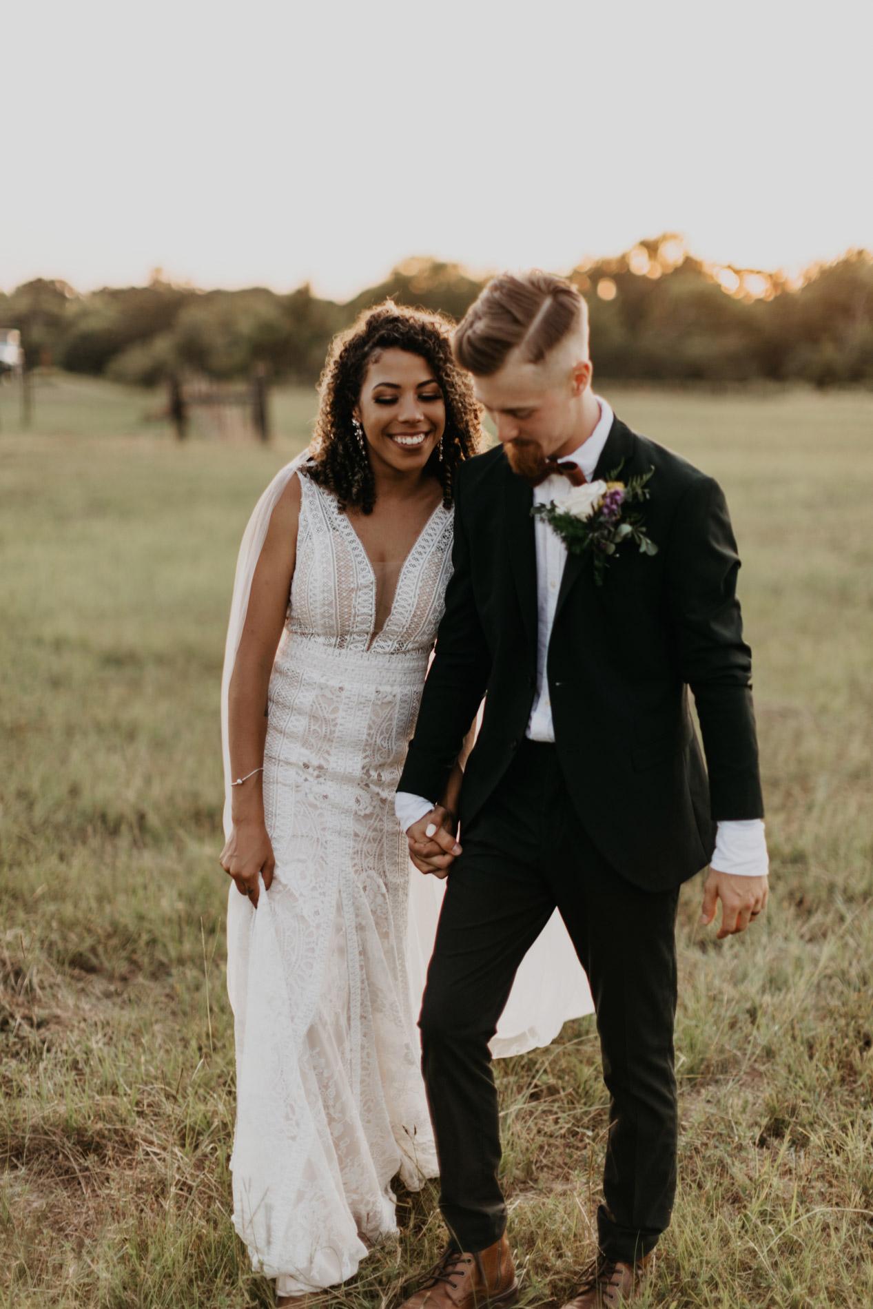 Bride and groom walking in field in East Texas