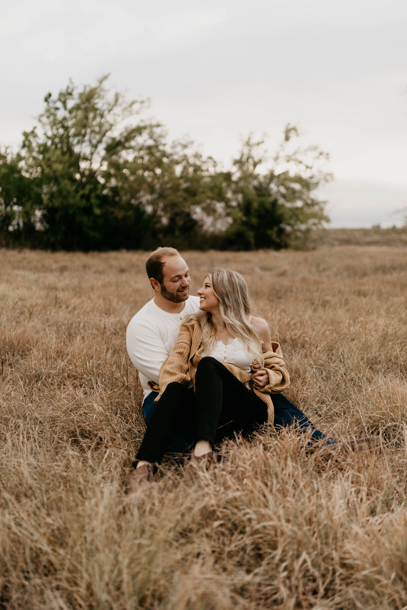 Couple sitting in golden grass wearing white shirts with black pants and cuddling during a fall engagement session