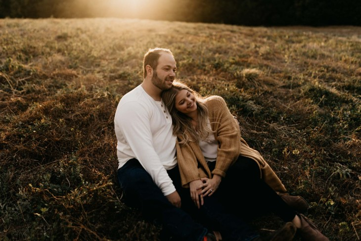 Cuddly girl and boy during fall engagement session at golden hour