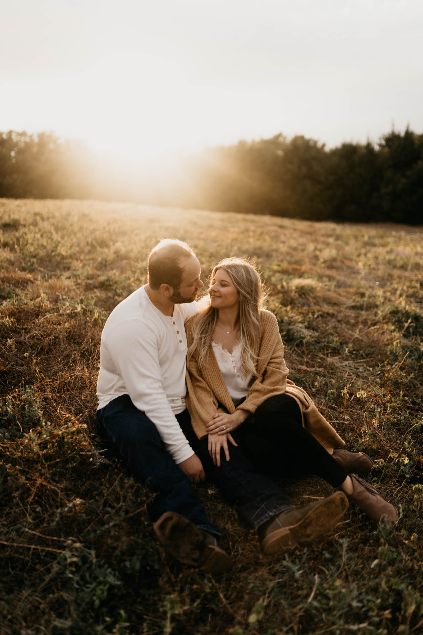 cute couple sitting in the grass wearing white sweaters at golden hour in the fall