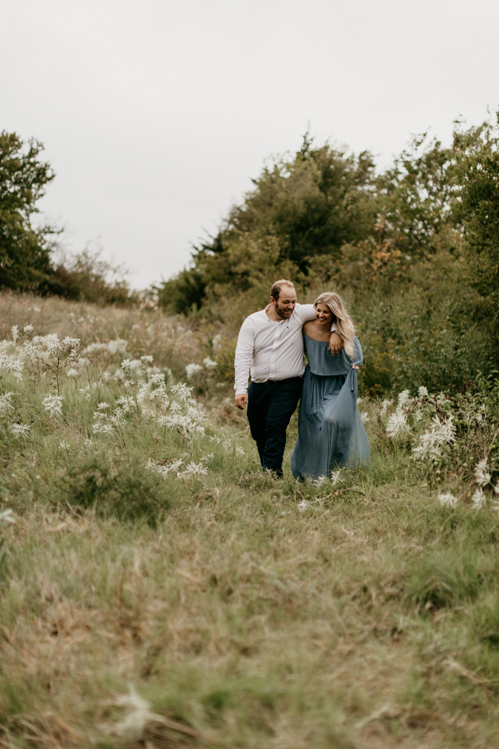Couple walking into a green field during their fall engagement session in north texas