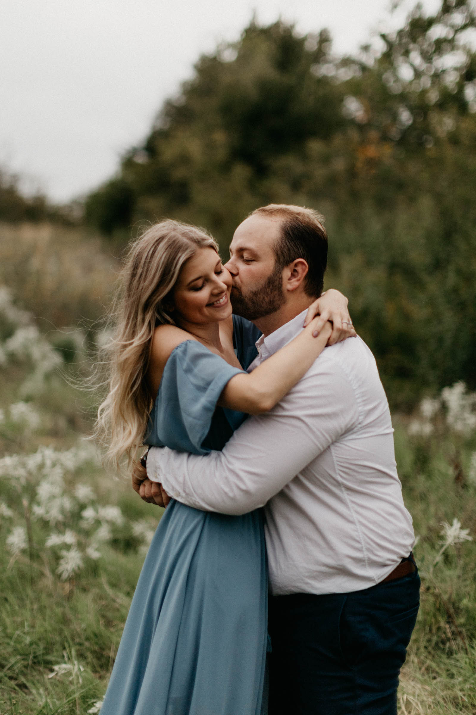 Boy kissing girl on the cheek during fall engagement session in fort worth | Couple wearing formal clothes for photography shoot