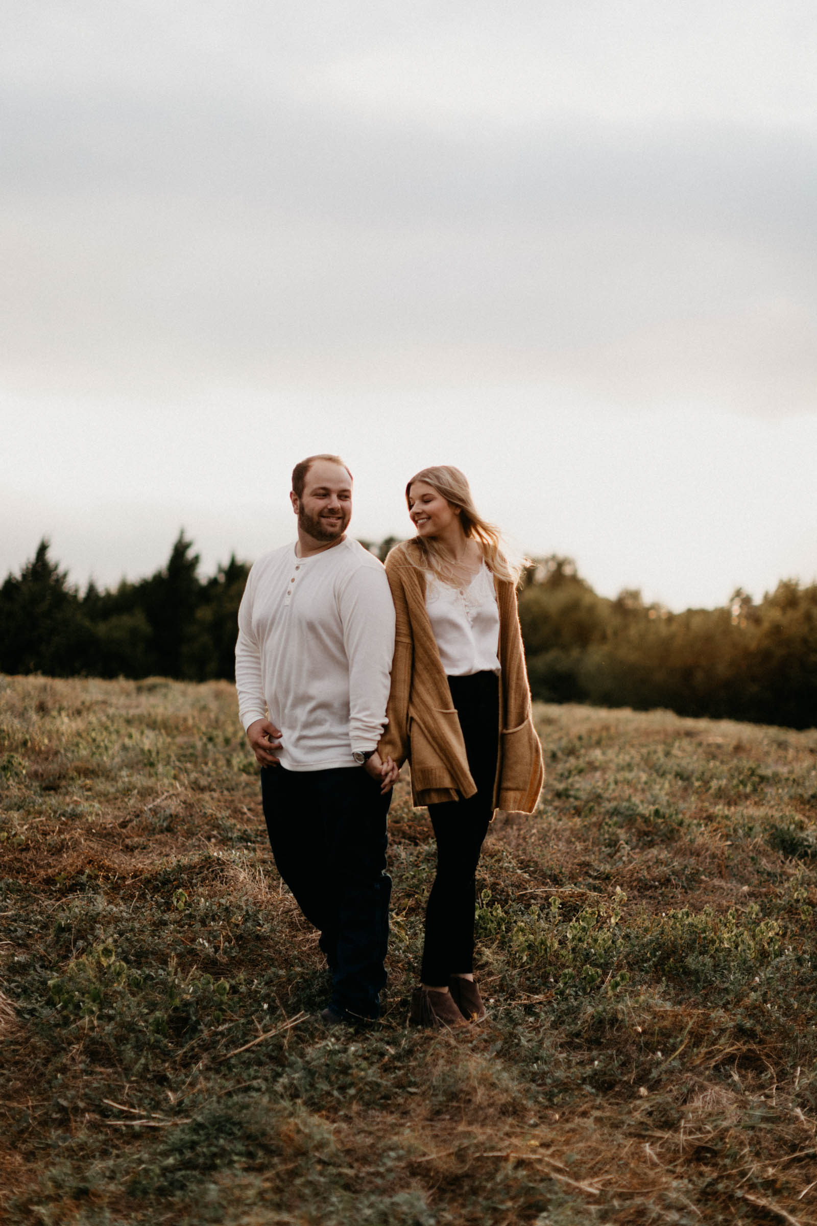 Couple standing back to back and looking at each other during their engagement session in north Texas