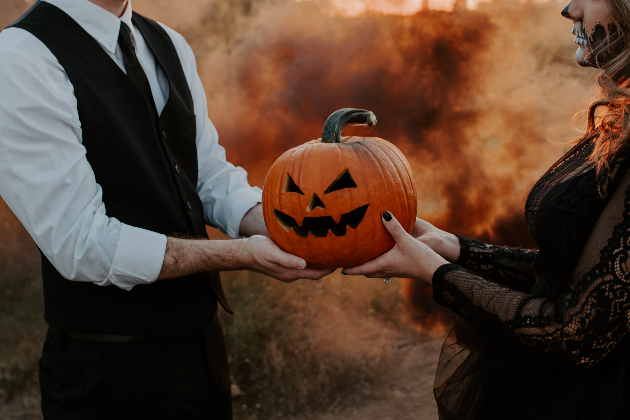 spooky couple holding pumpkin with black smoke bomb being lit by golden sunset