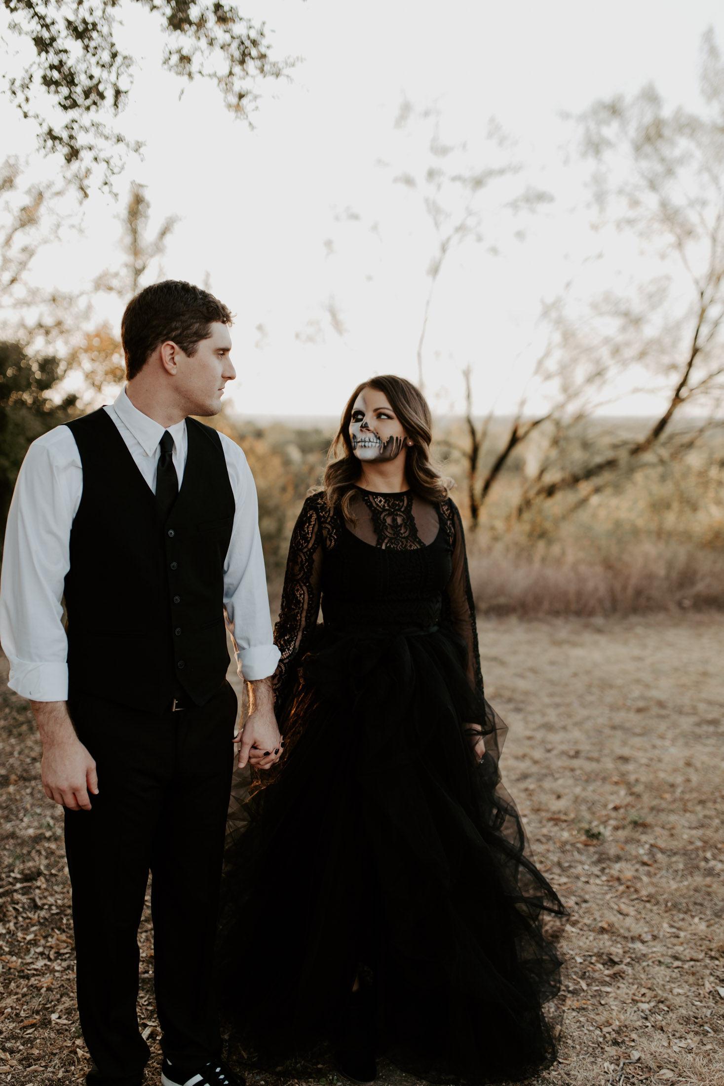 spooky skull makeup couple looking at each other in a park in dfw