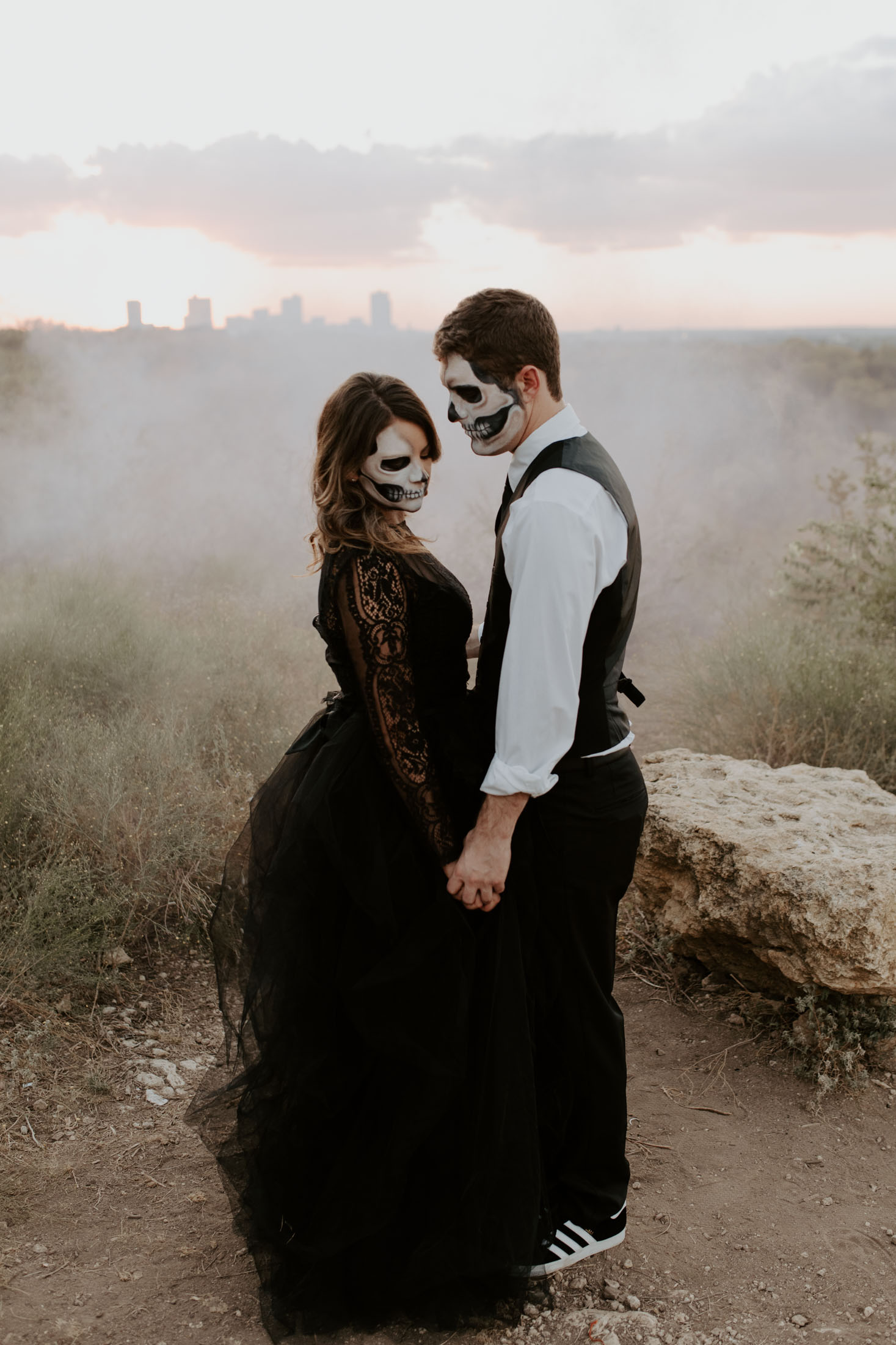 white smoke behind couple with skull makeup for halloween shoot