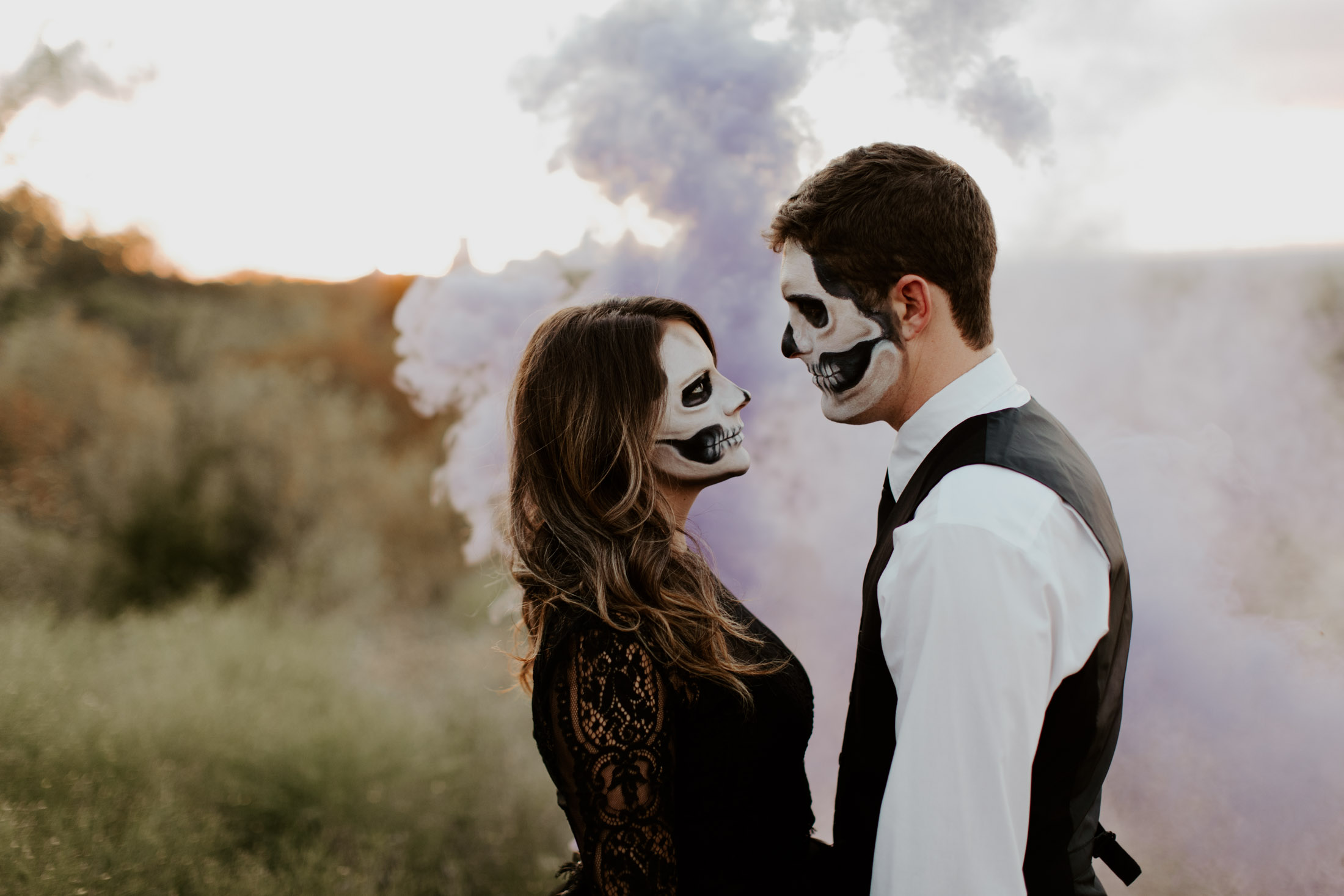 halloween themed couple looking t each other with purple smoke in the background