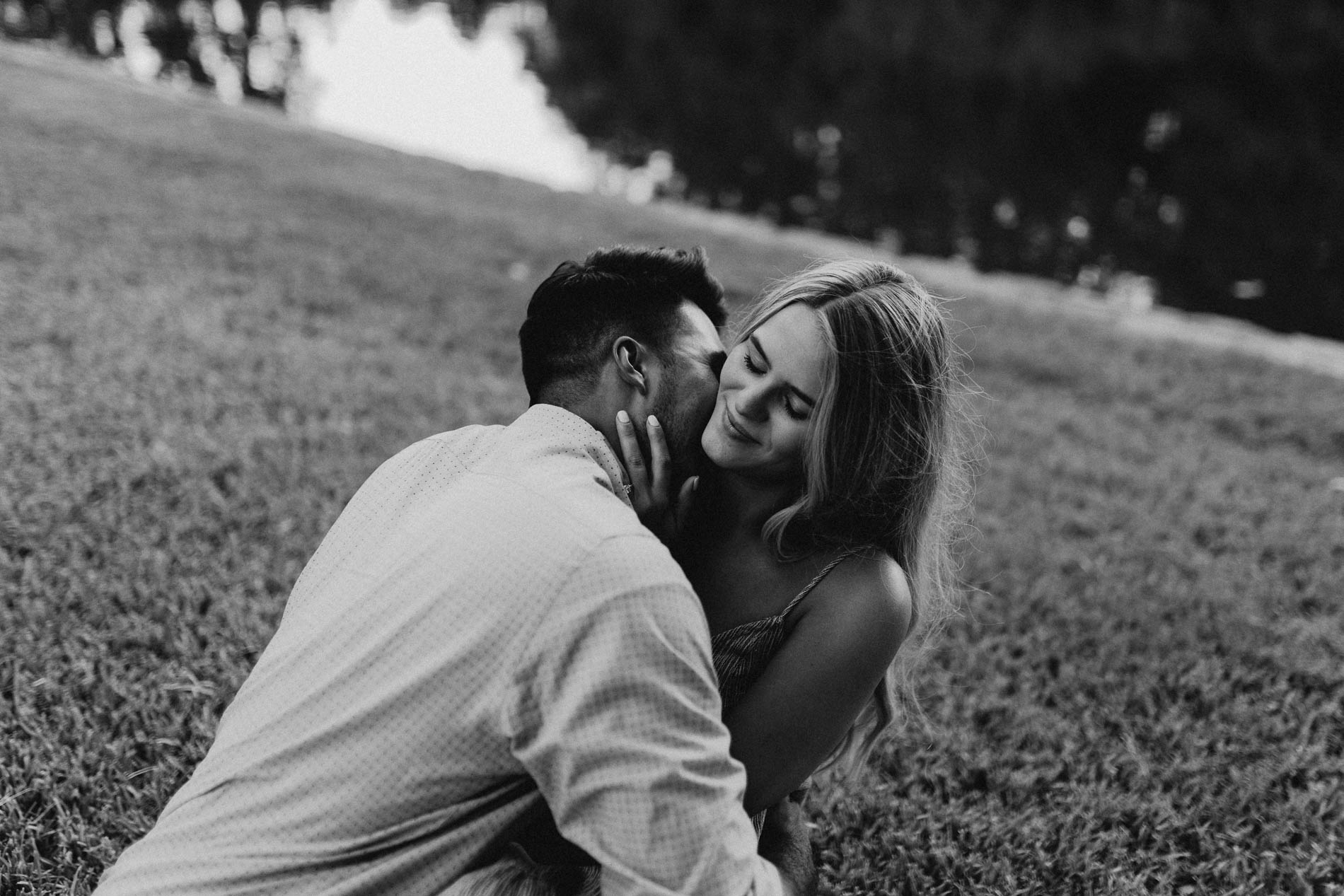 Black and white photo of couple being romantic in the grass during engagement session
