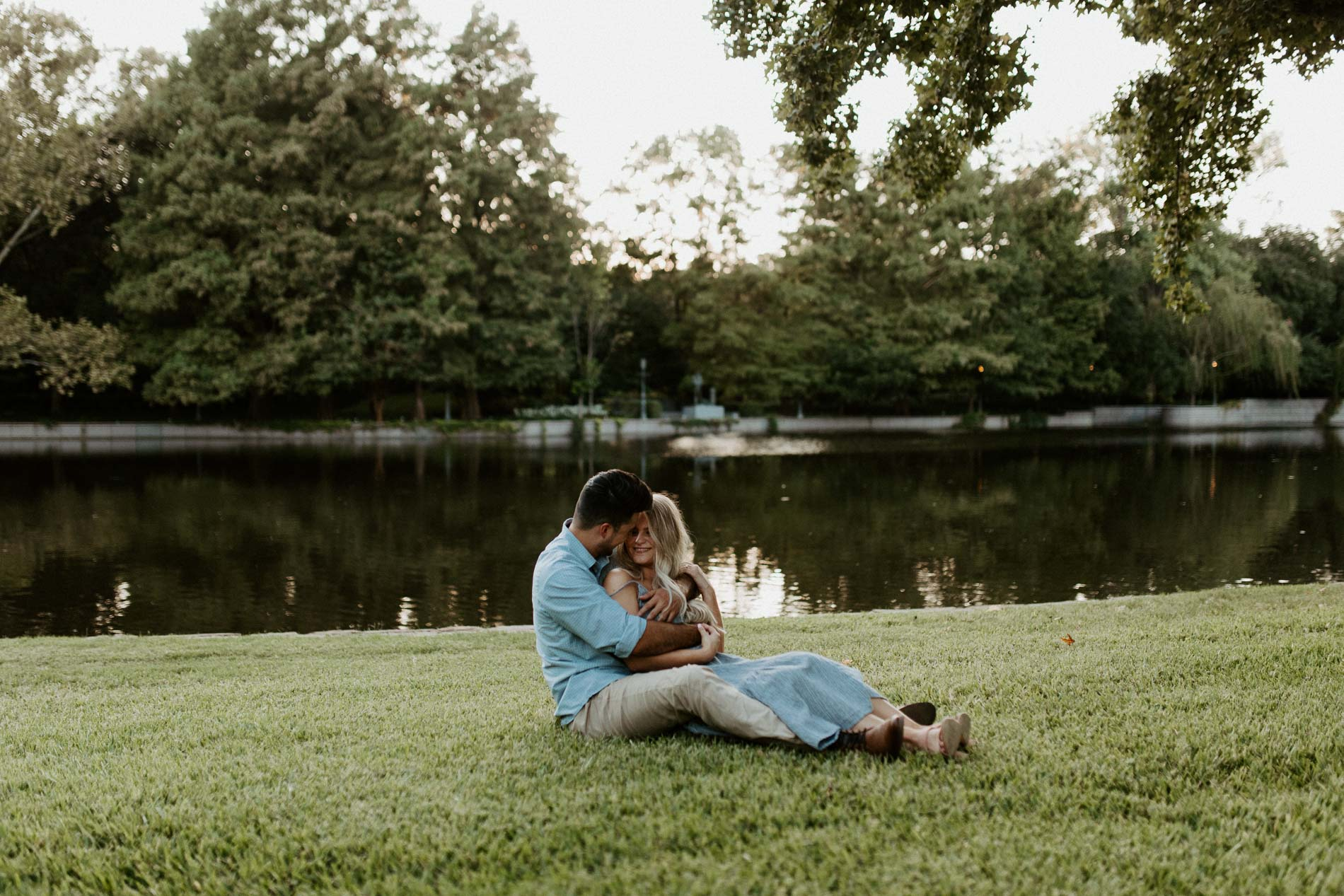 Couple sitting in green grass in front of a beautiful lake location